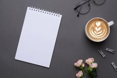White notepad with coffee and flowers on grey background in vintage style top view stock photography