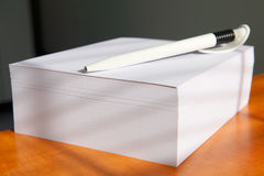 White notepad with a pen. On the table Stock Photos