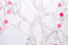 White notepad with pink decorations on a marble background in the office stock photo