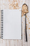 White notepad and spoon with oat flakes on wooden background Royalty Free Stock Images