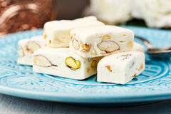 White Nougat. Pieces of white nougat served on a blue plate Royalty Free Stock Photos