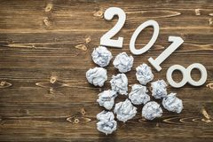 Number 2018 and crumpled paper on brown wooden board. Create ide stock image