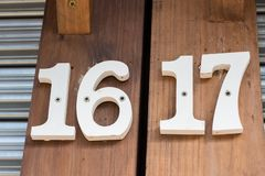 White numeral 16 / 17. Sixteen and seventeen, on brown wood royalty free stock images