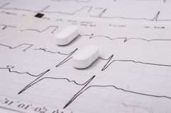 White oblong pills or tablets for treatment of diseases of the cardiovascular system as an option - statin lie on the paper elec. Trocardiogram EKG or ECG stock photos