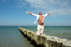 White ocean man. Man relaxing on woods on the blue sea having a rest royalty free stock photos