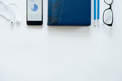 White office desk with glasses, mobile phone, earphones Royalty Free Stock Image