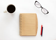 White office desk with a notebook and pencils, glasses Royalty Free Stock Image