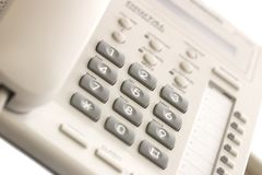 White office desk phone. On white background. Focus on the center button Royalty Free Stock Photo