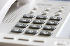 White office desk phone. Close-up. Focus on the center button Royalty Free Stock Photography