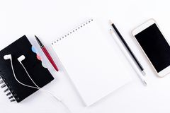 White office desk table with blank notebook, smart phones, headphones and other office supplies. Top view. Copy space. Flat lay.  royalty free stock images