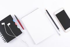 White office desk table with blank notebook, smart phones, headphones and other office supplies. Top view. Copy space. Flat lay royalty free stock images