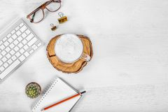 White office desk table with computer mouse and keyboard, cup of latte coffee, pencils and eye glasses. Top view with copy space, royalty free stock photos