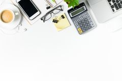 White office desk table with laptop, smartphone and supplies stock images