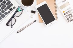 White office desk table, workspace office with laptop, smartphone black screen, pen, calculator, glasses, Top view with copy space.  royalty free stock images