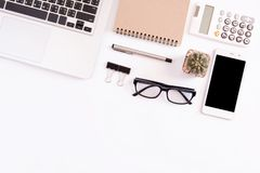 White office desk table, workspace office with laptop, smartphone black screen, pen, calculator, glasses, Top view with copy space.  royalty free stock photography