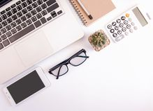 White office desk table, workspace office with laptop, smartphone black screen, pen, calculator, glasses, Top view with copy space.  stock photo
