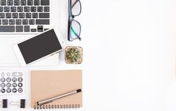 White office desk table, workspace office with laptop, smartphone black screen, pen, calculator, glasses, Top view with copy space.  stock image