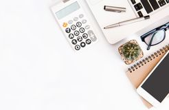 White office desk table, workspace office with laptop, smartphone black screen, pen, calculator, glasses, Top view with copy space.  stock images