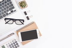 White office desk table, workspace office with laptop, smartphone black screen, pen, calculator, glasses, Top view with copy space.  stock photos
