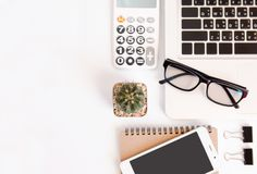 White office desk table, workspace office with laptop, smartphone black screen, pen, calculator, glasses, Top view with copy space.  stock photography