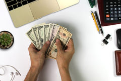White office desk with US Dollars Count , pen, laptop computer, Stock Photos