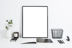 White office interior, stylish work table space with poster artw. Minimalist white office interior, stylish work table space with poster artwork mockup Royalty Free Stock Images
