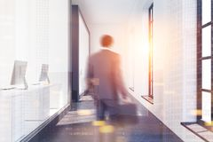 White office lobby interior toned. White office lobby with a concrete floor, glass and white doors and large windows. An African American businessman 3d Stock Photography