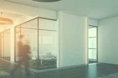 White office meeting room corner, people. Business people in a white conference room interior corner with a concrete floor, glass walls, a long table with white Royalty Free Stock Photo