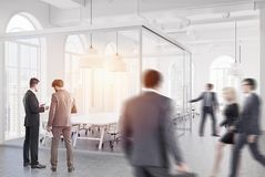 White office, meeting room, people. White open space office interior with loft windows, a wooden floor, an aquarium like conference room area and rows of Royalty Free Stock Photo