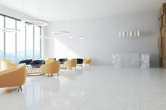 White office waiting area, reception. White office waiting area with a large door, a concrete floor, a round coffee table with yellow and black chairs near it. A Royalty Free Stock Image