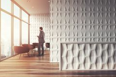 White office waiting room, businessman. White office waiting room interior with panoramic windows, a reception desk and brown armchairs near round coffee tables Royalty Free Stock Photo