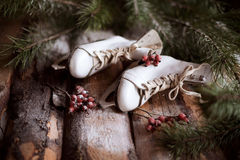 White ol-fashioned skates on wooden planks with spruce branches and red berries all around. Stock Images