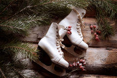 White ol-fashioned skates on wooden planks with spruce branches and red berries all around. Stock Photo
