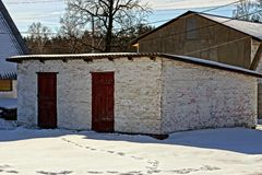 White old barn with red doors. Brick building in the yard with snow stock image