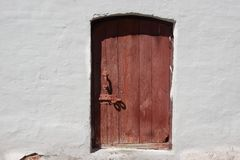 White old brick wall with weathered door or gate Stock Photography