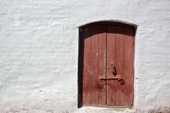 White old brick wall with weathered door or gate Stock Images