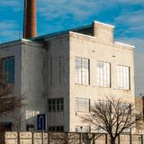 White old factory in Kaunas. White old factory and chimney in the back. Clear sky and sunny day. Kaunas city stock images
