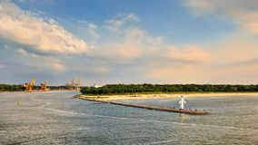 White old lighthouse in Swinoujscie, stone pier and wavy sea, Royalty Free Stock Images