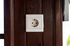 White old plastic power socket on a wooden wall outside. Bali. Royalty Free Stock Image