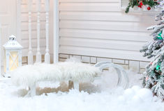 White old vintage sleigh with fur standing near the house in the snow in winter. Christmas decorations Stock Photo