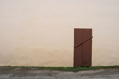 White old wall with closed door and grass Royalty Free Stock Photography