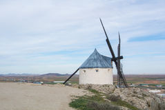 White old windmill on the hill near Consuegra. Castilla La Mancha, Spain, a symbol of region and journeys of Don Quixote Alonso Quijano and a town on cloudy day Royalty Free Stock Photo