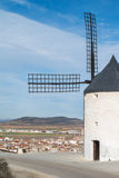 White old windmill on the hill near Consuegra. Castilla La Mancha, Spain, a symbol of region and journeys of Don Quixote Alonso Quijano and a town on cloudy day Stock Photography