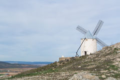 White old windmill on the hill near Consuegra. Castilla La Mancha, Spain, a symbol of region and journeys of Don Quixote Alonso Quijano on cloudy day Stock Photos