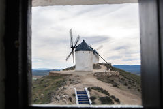 White old windmill on the hill near Consuegra. Castilla La Mancha, Spain, a symbol of region and journeys of Don Quixote Alonso Quijano and a town on cloudy day Royalty Free Stock Photos