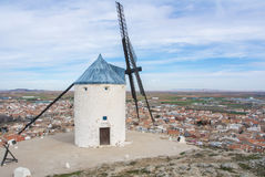 White old windmill on the hill near Consuegra. Castilla La Mancha, Spain, a symbol of region and journeys of Don Quixote Alonso Quijano and a town on cloudy day Stock Photos