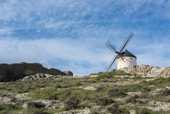 White old windmill on the hill near Consuegra. Castilla La Mancha, Spain, a symbol of region and journeys of Don Quixote Alonso Quijano on cloudy day Royalty Free Stock Photos