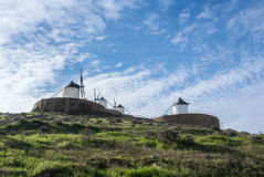 White old windmills on the hill near Consuegra. Castilla La Mancha, Spain, a symbol of region and journeys of Don Quixote Alonso Quijano on cloudy day Royalty Free Stock Images