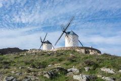 White old windmills on the hill near Consuegra. Castilla La Mancha, Spain, a symbol of region and journeys of Don Quixote Alonso Quijano on cloudy day Royalty Free Stock Photo