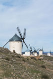 White old windmills on the hill near Consuegra. Castilla La Mancha, Spain, a symbol of region and journeys of Don Quixote Alonso Quijano on cloudy day Royalty Free Stock Photos